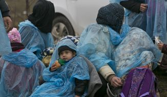 A migrant child and others covered with a plastic sheet to keep dry, rest during their walk from the Macedonian border into Serbia, near the village of Miratovac, Serbia, Wednesday, Jan. 6, 2016. Hundreds of migrants continue to arrive daily into Serbia in order to register and continue their journey further north towards Western Europe. (AP Photo/Visar Kryeziu)