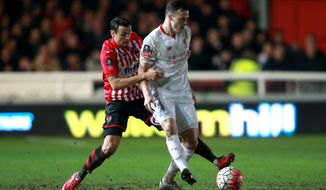 Exeter City's Alex Nicholls, left, and Liverpool's Brad Smith battle for the ball during the English FA Cup third round soccer match at St James Park, Exeter, England, Friday Jan. 8, 2016. (David Davies/PA via AP) UNITED KINGDOM OUT