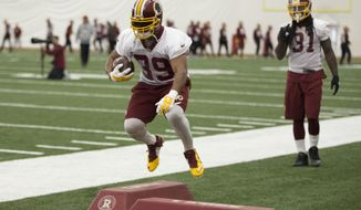 Washington Redskins running back Pierre Thomas participates in a footwork drill during practice at the team's NFL training facility at Redskins Park, on Friday, Jan. 8, 2016, in Ashburn, Va. The Washington Redskins will play the Green Bay Packers in a wild-card game on Sunday. At right is running back Matt Jones. (AP Photo/Evan Vucci)