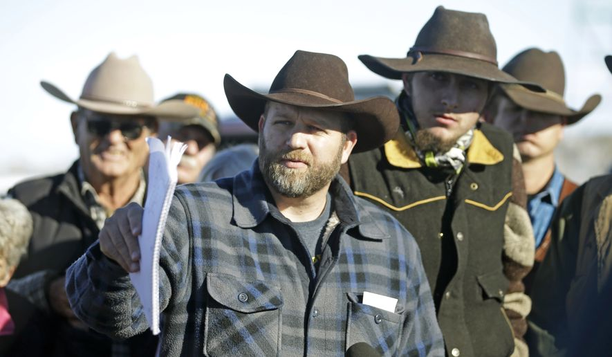 Ammon Bundy, center, speaks with a reporter at a news conference at Malheur National Wildlife Refuge Friday, Jan. 8, 2016, near Burns, Ore. Bundy, the leader of an armed group occupying the national wildlife refuge to protest federal land management policies, said Friday he and his followers are not ready to leave even though the sheriff and many locals say the group has overstayed their welcome. (AP Photo/Rick Bowmer)