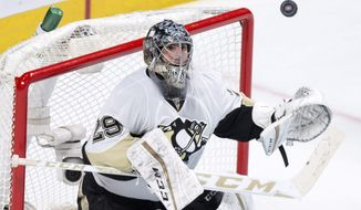 Pittsburgh Penguins goalie Marc-Andre Fleury eyes the puck during the third period of an NHL hockey game against the Montreal Canadiens on Saturday, Jan. 9, 2016, in Montreal. The Penguins won 3-1. (Paul Chiasson/The Canadian Press via AP)