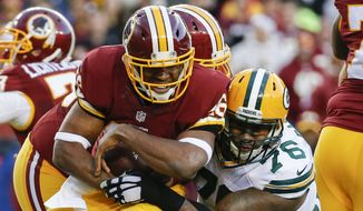 Washington Redskins running back Alfred Morris (46) is stopped by Green Bay Packers defensive end Mike Daniels (76) during the first half of an NFL wild card playoff football game in Landover, Md., Sunday, Jan. 10, 2016. (AP Photo/Alex Brandon)