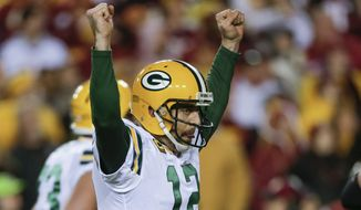 Green Bay Packers quarterback Aaron Rodgers (12) celebrates wide receiver Randall Cobb's touchdown during the first half of an NFL wild card playoff football game against the Washington Redskins in Landover, Md., Sunday, Jan. 10, 2016. (AP Photo/Mark Tenally)