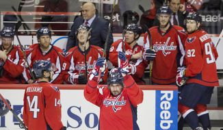 Washington Capitals left wing Alex Ovechkin (8), of Russia, acknowledges the fans in celebration as he comes back out of the box to a standing ovation after  Ovechkin scored his 500th career NHL goal during the second period of a hockey game against the Ottawa Senators in Washington, D.C., Sunday, Jan. 10, 2016. (AP Photo/Jacquelyn Martin)