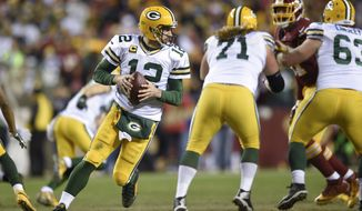 Green Bay Packers quarterback Aaron Rodgers (12) turns out of the pocket during the second half of an NFL wild card playoff football game against the Washington Redskins in Landover, Md., Sunday, Jan. 10, 2016. (AP Photo/Nick Wass)