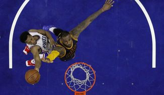 Philadelphia 76ers' Ish Smith, left, goes up to shoot against Cleveland Cavaliers' LeBron James during the first half of an NBA basketball game, Sunday, Jan. 10, 2016, in Philadelphia. (AP Photo/Matt Slocum)