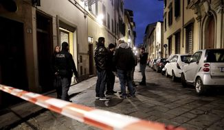 Italian police officers stand outside an apartment where 35-year-old American woman Ashley Oslen was found dead, in Florence, Italy, Saturday, Jan. 9, 2016. (Maurizio Degl'Innocenti/ANSA via AP
