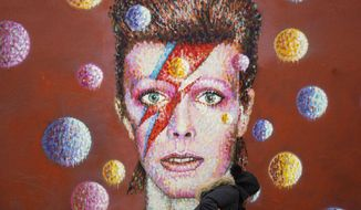 "Flowers are left below a mural of David Bowie on the wall of a Morley's store in Brixton, London, the singer's birthplace, after the rock star died, Monday Jan. 11, 2016.  Bowie, the iconic and shape-shifting British singer whose illustrious career lasted five decade with hits like ""Fame,"" ''Heroes"" and ""Let's Dance,"" died Sunday, Jan. 10, 2016,  after a battle with cancer. He was 69. (Anthony Devlin/PA via AP)"