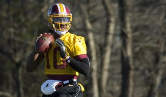 FILE - In this Jan. 6, 2016 file photo, Washington Redskins quarterback Robert Griffin III eyes the receiver during NFL football practice at Redskins Park in Ashburn, Va. Griffin has cleared out his locker at Redskins Park and is expected to be let go by the team that dealt a trove of draft picks for the right to pick him No. 2 overall in  2012. (AP Photo/Manuel Balce Ceneta, File)