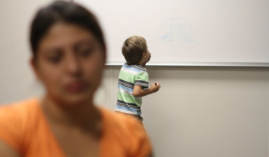 """A woman from Guatemala who declined to give her name for this photo talks while her son paints on a whiteboard at the Artesia Family Residential Center, a federal detention facility for undocumented immigrant mothers and children in Artesia, N.M, Wednesday, Sept. 10, 2014. The center has been held up by the Obama Administration as visible example of a crackdown on illegal crossings from Central America, while civil rights advocates are suing the federal government, complaining that lack of access to legal representation has turned the Artesia center into a """"deportation mill."""" (AP Photo/Juan Carlos Llorca)"""