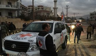 This picture provided by The International Committee of the Red Cross (ICRC), working alongside the Syrian Arab Red Crescent (SARC) and the United Nations (UN), shows a convoy containing food, medical items, blankets and other materials being delivered to the town of Madaya in Syria, Monday, Jan. 11, 2016. (ICRC via AP)