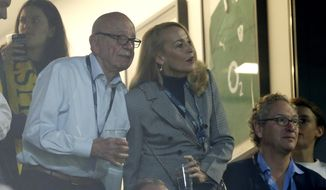 Media mogul Rupert Murdoch stands with model Jerry Hall during the Rugby World Cup final between New Zealand and Australia at Twickenham Stadium, London, during this Nov. 1, 2015, file photo. Murdoch has announced his engagement to Hall, the actress and former supermodel who had a long-time relationship with Mick Jagger, Monday, Jan. 11, 2016. (AP Photo/Alastair Grant, File)