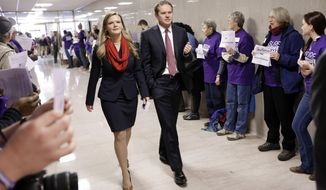 Rep. Jeremy Durham, R-Franklin, and his wife, Dr. Jessica Durham, walk past protesters advocating for the passage of Gov. Bill Haslam's Medicaid expansion proposal as the Durhams walk to the Capitol on the opening day of the second session of the 109th General Assembly Tuesday, Jan. 12, 2016, in Nashville, Tenn. Rep. Durham was the sponsor of the law that required Haslam to seek Legislative approval for any effort to seek Medicaid expansion. (AP Photo/Mark Humphrey) **FILE**