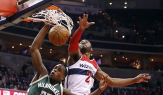 Milwaukee Bucks guard Khris Middleton (22) dunks in front of Washington Wizards guard John Wall during the first half of an NBA basketball game, Wednesday, Jan. 13, 2016, in Washington. (AP Photo/Alex Brandon)