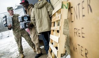 Michigan National Guard Staff Sgt. Stephen Robel, left, holds the door open while helping Flint resident Herbert Biggs, 59, as they carry cases of free bottled water to his truck as the first seven Michigan National Guard soldiers are on the ground at fire stations on Wednesday, Jan. 13, 2016 throughout the city, assigned by Gov. Rick Snyder on Tuesday to help distribute water and relieve residents in relation to the Flint water crisis. Safe drinking water has not flowed from many Flint faucets for almost two years after the state-run city switched its source to the highly corrosive Flint River and failed to treat it properly to protect lead from leaching into it. (Jake May/The Flint Journal-MLive.com via AP)