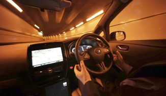 In this Nov. 3, 2015 file photo, Nissan Motor Co. General Manager Tetsuya Iijima takes his hands off of the steering wheel of a self-driving prototype vehicle during a test drive in Tokyo. (AP Photo/Eugene Hoshiko, File)