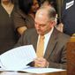 Louisiana Gov. John Bel Edwards signs an executive order in Baton Rouge on his first full day in office Tuesday, starting the process for expanding Louisiana's Medicaid program as allowed under the federal health care law. (Associated Press)