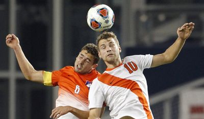 Clemson midfielder Paul Clowes (6) and Syracuse midfielder Julian Buescher (10) go up for the ball in the first half of an NCAA College Cup soccer match, Friday, Dec. 11, 2015, in Kansas City, Kan. (AP Photo/Colin E. Braley)