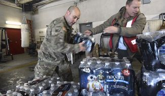 Michigan Nation Guard Sgt. Steve Kiger, left, of Harrison, Mich., stacks cases of drinking water with Red Cross volunteer Franklin Dickerson of Pleasant Ridge Wednesday Jan 13, 2016 in Flint, Mich. Members of the Michigan National Guard began arriving in Flint on Wednesday for briefings on the drinking water crisis, ahead of a larger contingent of Guardsmen who will help distribute bottled water, filters and other supplies to residents. (Dale G. Young/Detroit News via AP)  DETROIT FREE PRESS OUT; HUFFINGTON POST OUT; MANDATORY CREDIT