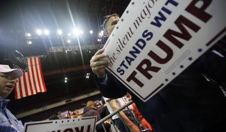 Supporters hand out placards during Republican presidential candidate Donald Trump's campaign rally at the Pensacola Bay Center in Pensacola, Fla., Wednesday, Jan. 13, 2016. (AP Photo/Michael Snyder)