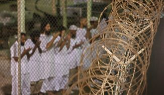 Guantanamo detainees pray before dawn near a fence of razor-wire, inside Camp 4 detention facility at Guantanamo Bay U.S. Naval Base, Cuba, in this May 14, 2009, file photo reviewed by the U.S. military. (AP Photo/Brennan Linsley, File)