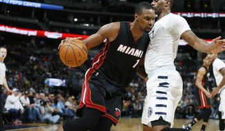 Miami Heat forward Chris Bosh, left, drives the lane as Denver Nuggets forward Darrell Arthur defends during the first half of an NBA basketball game Friday, Jan. 15, 2016, in Denver. (AP Photo/David Zalubowski)