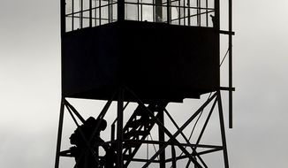 A member of the group occupying the Malheur National Wildlife Refuge headquarters stands on a watch tower at the refuge near Burns, Ore., in this Jan. 8, 2016, file photo. (AP Photo/Rick Bowmer, File)