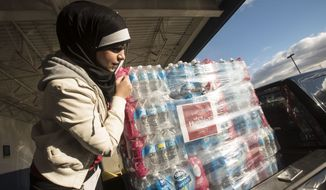 A volunteer for the Who is Hussain campaign, Balssam Fatlawi, 26, helps prepare water for donation to the Red Cross in Flint, Michigan on Sunday. (Courtesy of Mohammed Almawla)