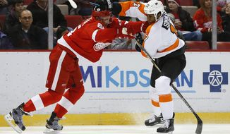 Detroit Red Wings defenseman Danny DeKeyser (65) checks Philadelphia Flyers right wing Wayne Simmonds (17) in the first period of an NHL hockey game, Sunday, Jan. 17, 2016 in Detroit. (AP Photo/Paul Sancya)