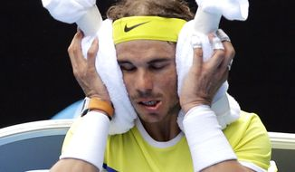 Rafael Nadal of Spain warps ice towels around his face during a break in his first round match against compatriot Fernando Verdasco at the Australian Open tennis championships in Melbourne, Australia, Tuesday, Jan. 19, 2016.(AP Photo/Aaron Favila)
