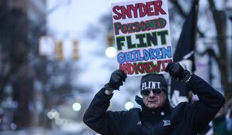 Mike Ahrens of Muskegon, Mich., poses for photo with his sign about Flint's water crisis Monday, Jan. 18, 2016, in Ann Arbor, Mich. Michigan Gov. Rick Snyder responded Monday to criticism from presidential candidate Hillary Clinton during the Democratic debates for his handling of Flint's water emergency, saying Clinton is making it a political issue. (Junfu Han/The Ann Arbor News via AP)