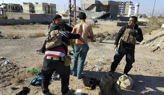 In this Wednesday, Jan. 13, 2016 file photo, a wounded civilian is treated by Iraqi security forces after he was shot by Islamic State group fighters as he was trying to cross from neighborhoods under control of Islamic State group to neighborhoods under control of Iraqi security forces in Ramadi, 70 miles (115 kilometers) west of Baghdad, Iraq. (AP Photo)