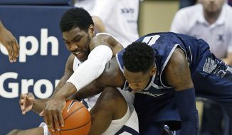 Xavier guard Remy Abell (10) and Georgetown guard L.J. Peak (0) fight for control of a loose ball during the first half of an NCAA college basketball game Tuesday, Jan. 19, 2016, in Cincinnati. (AP Photo/Gary Landers)