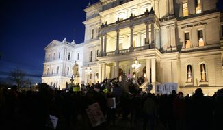 Protesters gather outside the state Capitol before Michigan Gov. Rick Snyder's State of the State address, Tuesday, Jan. 19, 2016, in Lansing, Mich. (AP Photo/Al Goldis)