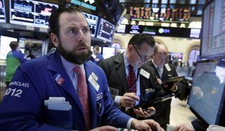 Specialist Michael Pistillo, left, works with traders at his post on the floor of the New York Stock Exchange, Wednesday, Jan. 20, 2016. Energy stocks are leading another sell-off on Wall Street as the price of oil continues to plunge. (AP Photo/Richard Drew)
