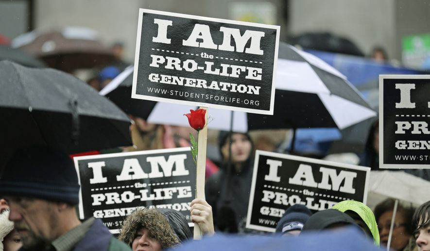 A pro-life demonstrator holds a sign and a flower while cheering during a rally, Tuesday, Jan. 19, 2016, at the Capitol in Olympia, Wash. (AP Photo/Ted S. Warren) ** FILE **