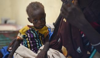 Nyagoah Taka Gatluak, a severely malnourished one-year-old child, sits on her mother's lap in the Doctors Without Borders clinic in Leer town, South Sudan on Dec. 15. Leer is experiencing famine conditions. (Associated Press)