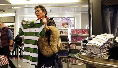 In this Wednesday, Dec. 2, 2015, file photo, a woman shops in an Aeropostale clothing store, in New York. The Labor Department reports on consumer prices for December, on Wednesday, Jan. 20, 2016. (AP Photo/Mark Lennihan)