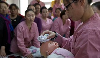 In this photo taken Friday, Dec. 11, 2015, maternity matrons use a doll as they learn to take care of babies during training classes run by Li Ming Maternity Service Company in Beijing, China. Now that China has abandoned its decades-long one-child policy, demand for maternity services is expected to increase as women take advantage of the chance to have a second child. (AP Photo/Ng Han Guan)