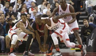 Miami Heat's Dwyane Wade, second from left, gathers the ball under pressure from Toronto Raptors' Kyle Lowry, left, Terrence Ross (31) and Bismack Biyombo (8) during the first half of an NBA basketball game Friday, Jan. 22, 2016, in Toronto. (Chris Young/The Canadian Press via AP)