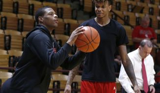 In this photo taken Jan. 2, 2016, North Carolina State's Dennis Smith Jr., left, shoots as Shaun Kirk watches during warmups before the Wolfpack's game against Virginia Tech at Cassell Coliseum in Blacksburg, Va. While his teammates head into Saturday's game against No. 20 Duke hoping to dig out from a 1-5 ACC start, Smith is trying to help from the sidelines and get ready to play next season. (Ethan Hyman/The News & Observer via AP) MANDATORY CREDIT  MBO  (REV-SHARE)