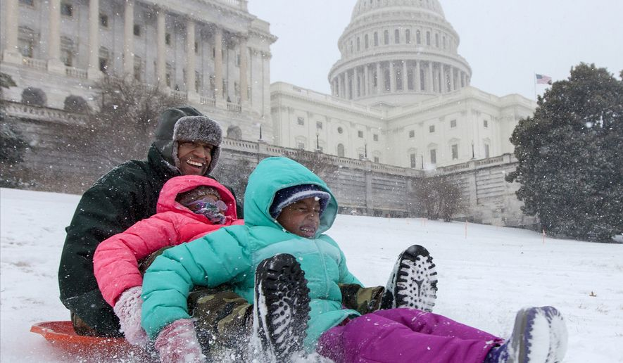 FILE - In this Jan. 21, 2014 file photo, Bashon Mann and his children sled down a hill on Capitol Hill in Washington as snow falls. It may have taken an act of Congress, but the children of Washington are finally welcome to go sledding on Capitol Hill. With a major blizzard bearing down on Washington, the U.S. Capitol Police on Thursday told the public that they won't be enforcing, as in years past, a longstanding sledding ban. Existing law officially forbids sledding in order to protect the Capitol grounds, but lawmakers instructed the cops to chill out in legislation that cleared Congress last month.  (AP Photo/J. Scott Applewhite, File)