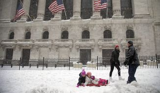 Anthony Pino, right, pulls Simone, 2, right, and Serena, 5, center, with their friend Annabelle Hussian, on a sled along Broad Street in front of the New York Stock Exchange as Lissa Hussian follows along during a snow storm, Saturday, Jan. 23, 2016, in New York. (AP Photo/Julie Jacobson)
