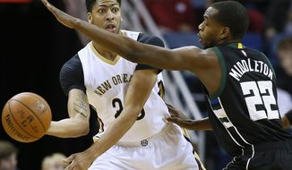 New Orleans Pelicans forward Anthony Davis (23) looks to pass around Milwaukee Bucks guard Khris Middleton (22) during the first half of an NBA basketball game Saturday, Jan. 23, 2016, in New Orleans. (AP Photo/Jonathan Bachman)