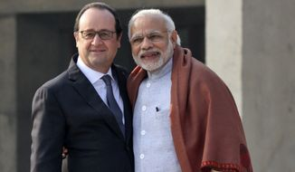 """French President Francois Hollande, left, poses with Indian Prime Minister Narendra Modi, during a visit to the Capitol Complex in Chandigarh, India, Sunday, Jan.24, 2016. Hollande began a three-day visit to India on Sunday. Designed in the 1950s by Swiss-French architect Le Corbusier, Chandigarh is one of three places that France has pledged to help develop as so-called """"smart cities"""" — with clean water supplies, efficient sewage disposal and public transportation. (AP Photo/Kapil Sethi)"""