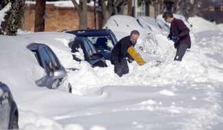 People dig out their cars Sunday in Alexandria, Va. Millions of Americans were preparing to dig themselves out Sunday after a mammoth blizzard with hurricane-force winds and record-setting snowfall brought much of the East Coast to an icy standstill. (Associated Press)
