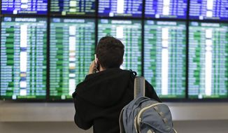 A traveler speaks on the phone as he views the arrival and departure board Friday, Jan. 22, 2016, at San Francisco International airport in San Francisco. Dozens of flights have been canceled and delayed at San Francisco International Airport because of the blizzard that was set to rip across the East Coast. (AP Photo/Ben Margot) ** FILE **