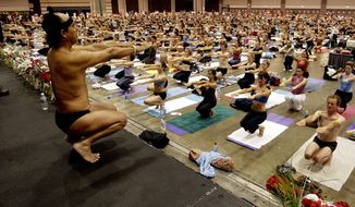 In this Sept. 27, 2003, file photo, Bikram Choudhury, front, founder of the Yoga College of India and creator and producer of Yoga Expo 2003, leads what organizers hope will be the world's largest yoga class at the Expo at the Los Angeles Convention Center. (AP Photo/Reed Saxon, File)