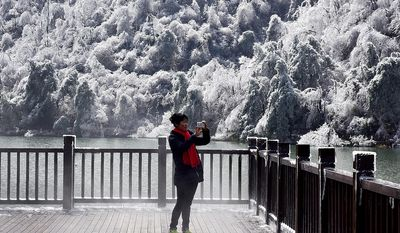 A woman uses a smartphone to take a souvenir photo of the trees covered with ice at a resort in Hangzhou in east China's Zhejiang province, Monday, Jan. 25, 2016. (Chinatopix via AP) CHINA OUT
