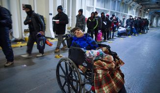 A child in a wheelchair waits as migrants queue up to have their tickets checked as they board the ferry to Athens, on Lesbos Island, Greece, Sunday, Jan. 24, 2016. (AP Photo/Mstyslav Chernov)